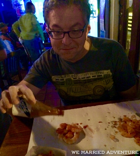 Mike enjoying fresh Gulf peel-and-eat shrimp with Crystal hot sauce.